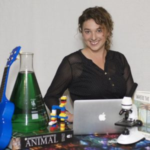 Jen Tuttle Parsons sits smiling with a laptop, a microscope, books, LEGOs, and an Erlenmeyer flask