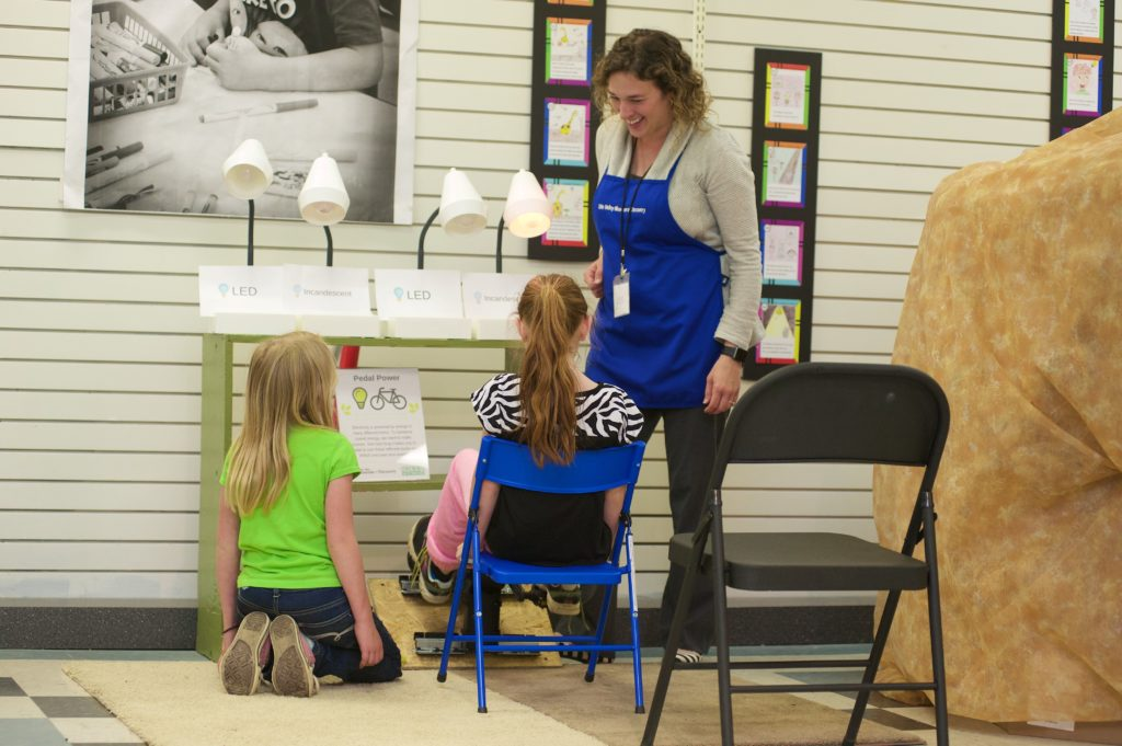 Jen, in blue apron, speaks to two young museum guests while demonstrating an exhibit comparing LED, incandescent, and fluorescent light bulbs.